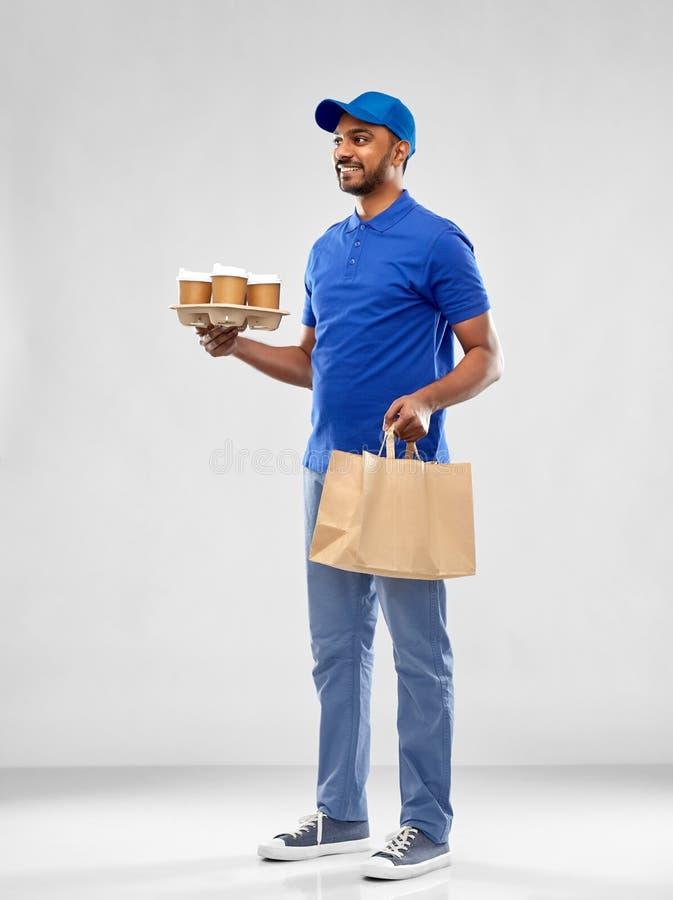 Счастливый индийский работник доставляющий покупки на дом с едой и напитками стоковые изображения rf