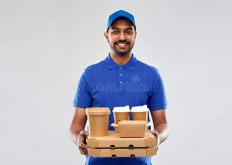 Счастливый индийский работник доставляющий покупки на дом с едой и напитками стоковое изображение rf
