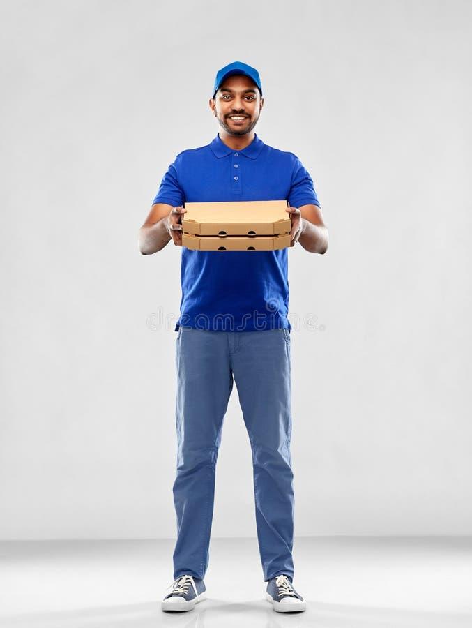 Счастливый индийский работник доставляющий покупки на дом с коробками пиццы в сини стоковое изображение rf