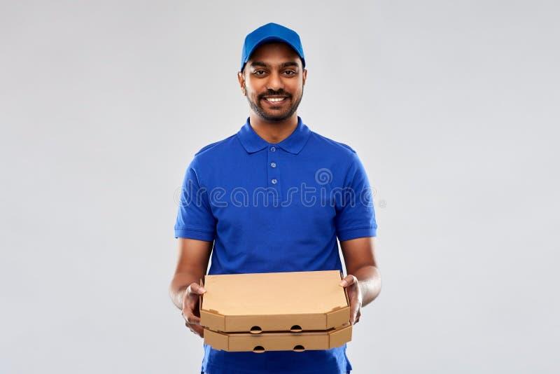 Счастливый индийский работник доставляющий покупки на дом с коробками пиццы в сини стоковые изображения rf