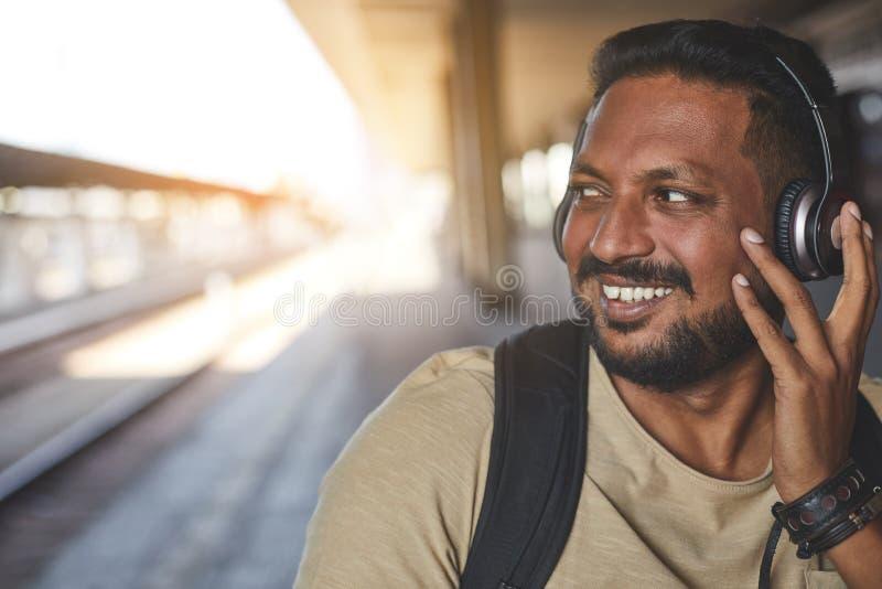 Счастливый индусский человек нося его современные наушники стоковое фото rf