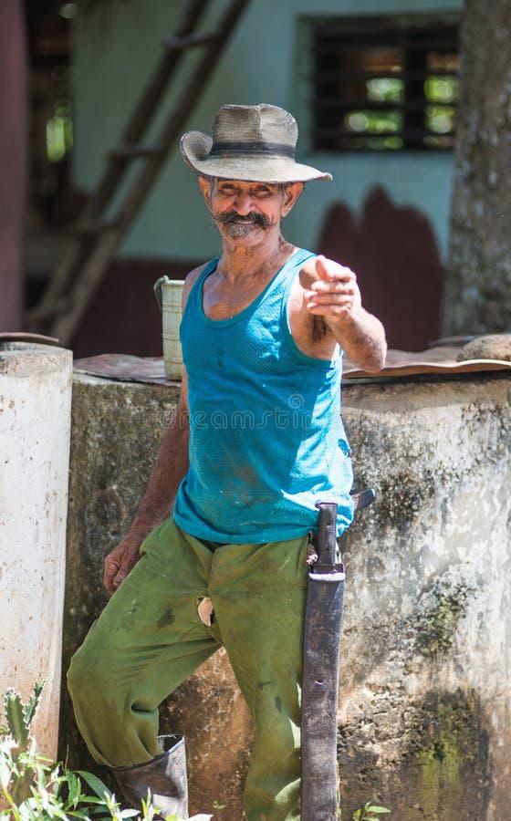 Счастливый и дружелюбный кубинський старший фермер и выхолить портрет захвата человека в старой плохой долине, Кубе, Америке стоковое изображение rf