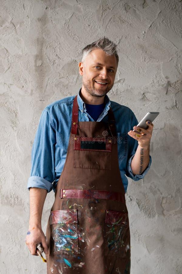 Счастливый и успешный художник со смартфоном и кистью стоковые фото