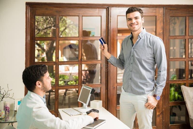 Счастливый клиент оплачивая с кредитной карточкой стоковые изображения rf