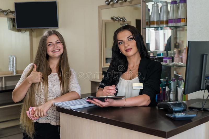 Счастливый клиент с администратором около таблицы приема стоковые фотографии rf