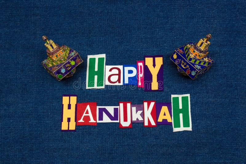 СЧАСТЛИВЫЙ коллаж с красочными dreidels, multi покрашенная ткань текста слова ХАНУКИ на голубой джинсовой ткани, еврейском праздн стоковое изображение rf