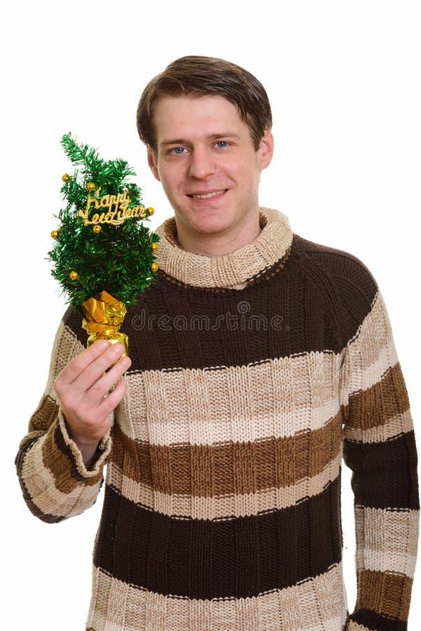 Счастливый красивый кавказский человек держа С Новым Годом! дерево стоковое фото