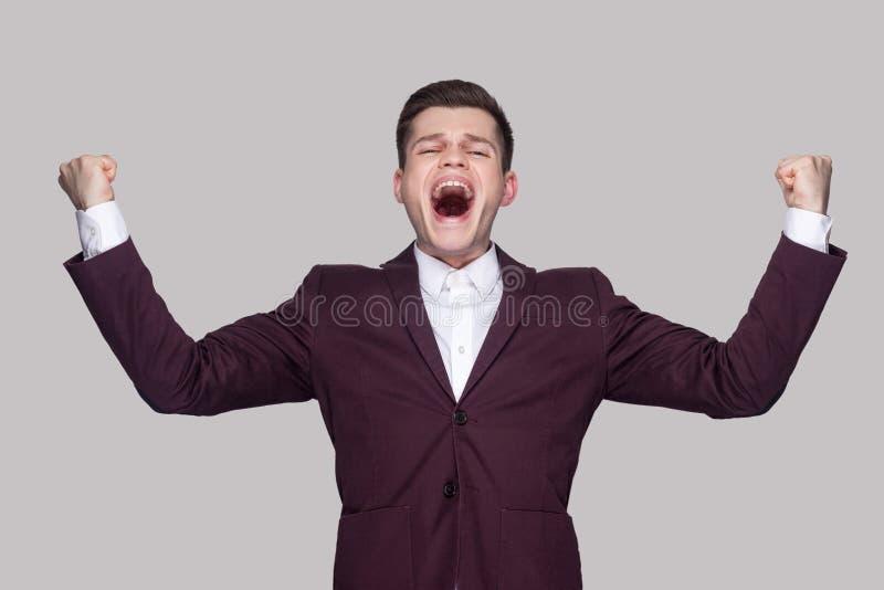 Счастливый красивый молодой человек в фиолетовом костюме и белой рубашке, дежурном стоковое изображение