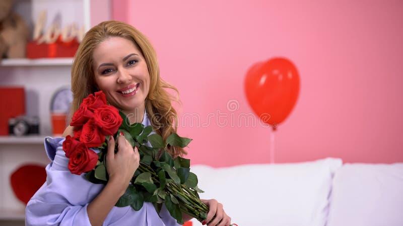 Счастливый красивый пук удерживания женщины красных роз и усмехаться к камере, романс стоковое фото rf