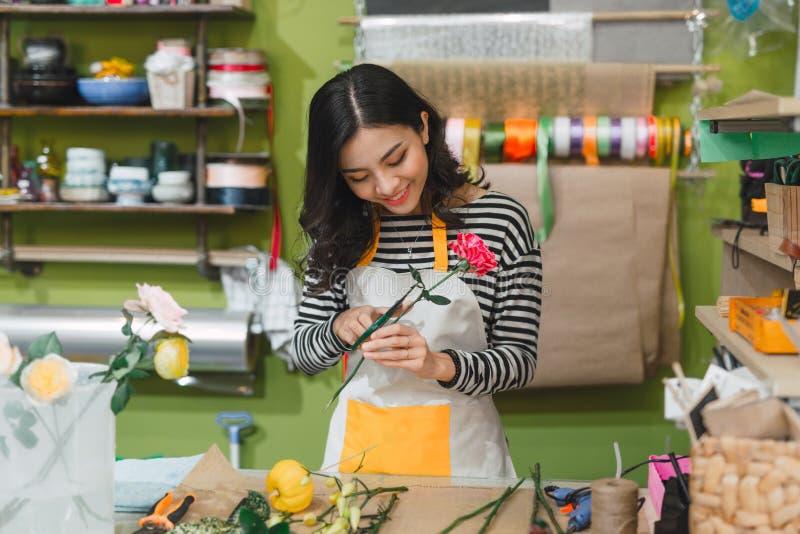 Счастливый красивый флорист молодой женщины стоя в цветочном магазине стоковое изображение rf