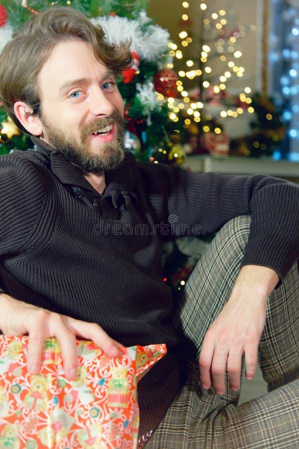 Счастливый красивый человек с голубыми глазами и длинной съемкой ночи рождества бороды и волос дома усмехаясь широкой стоковое фото rf