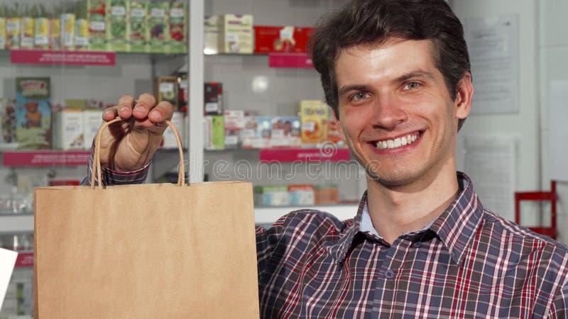 Счастливый красивый человек усмехаясь держащ хозяйственную сумку на фармации стоковые фото