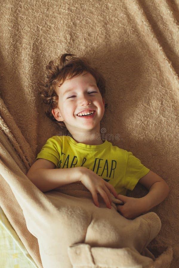 Счастливый курчавый младенец малыша имея потеху в кровати усмехаться мальчика милый Вертикальное фото стоковые изображения rf