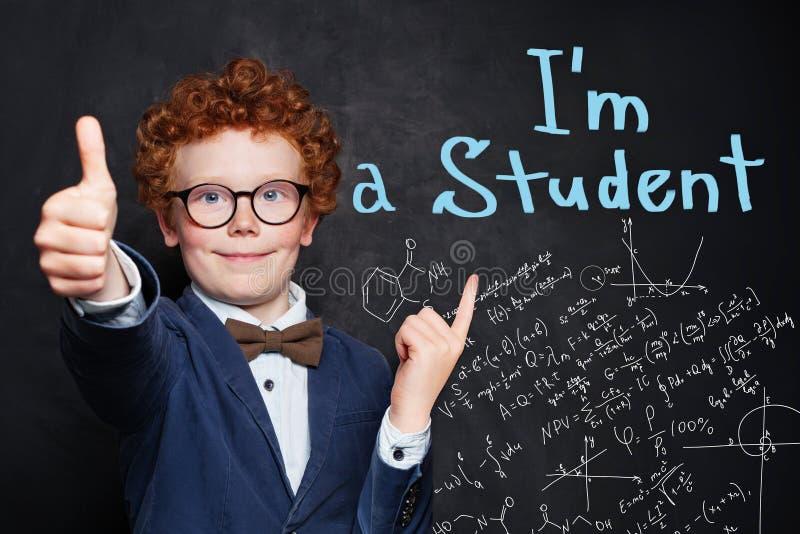 Счастливый любопытный мальчик ребенка на предпосылке классн классного с формулами науки и математик стоковое изображение rf