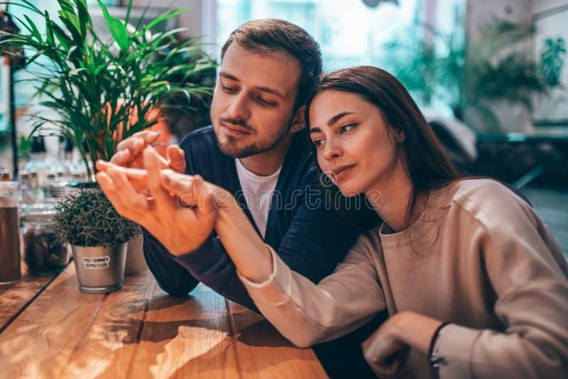 Счастливый любящий парень держит руку его девушки сидя на таблице в кафе и смотрит ее стоковая фотография rf