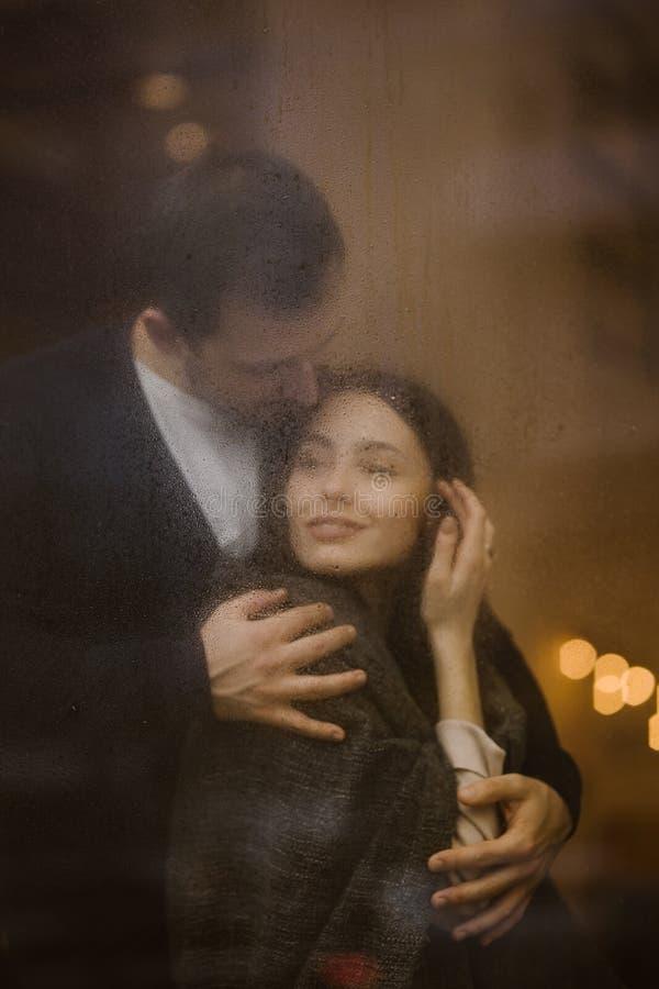 Счастливый любящий парень обнимает его положение девушки за влажным окном со светами стоковые изображения