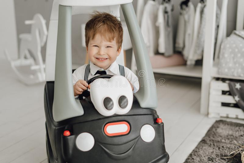 Счастливый маленький кавказский мальчик управляя смешным автомобилем игрушки стоковые изображения rf