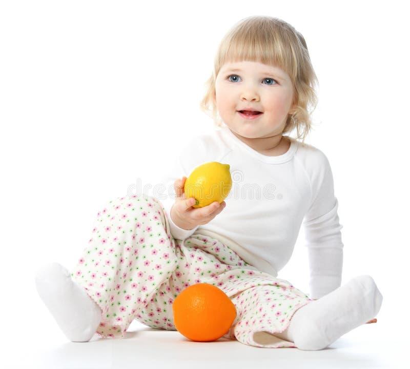 Счастливый маленький младенец играя с плодоовощами стоковая фотография