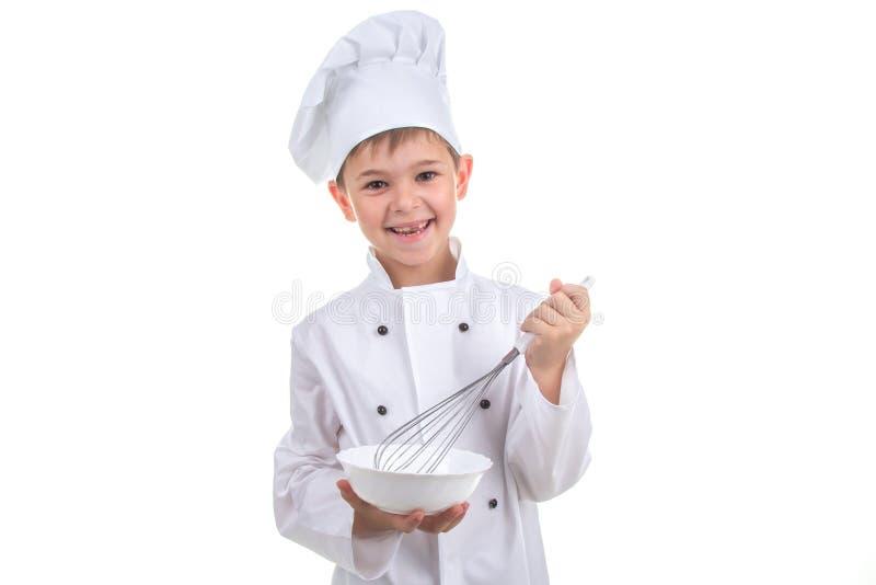 Счастливый маленький шеф-повар смешивая что-то с юркнуть, на белой предпосылке стоковые фото