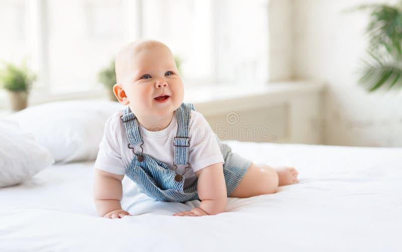 Счастливый малыш младенца в кровати стоковые фотографии rf