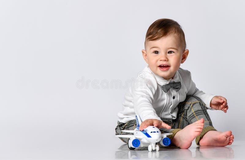 Счастливый малыш ребенка играя с самолетом игрушки и мечтая быть пилотом стоковое фото rf