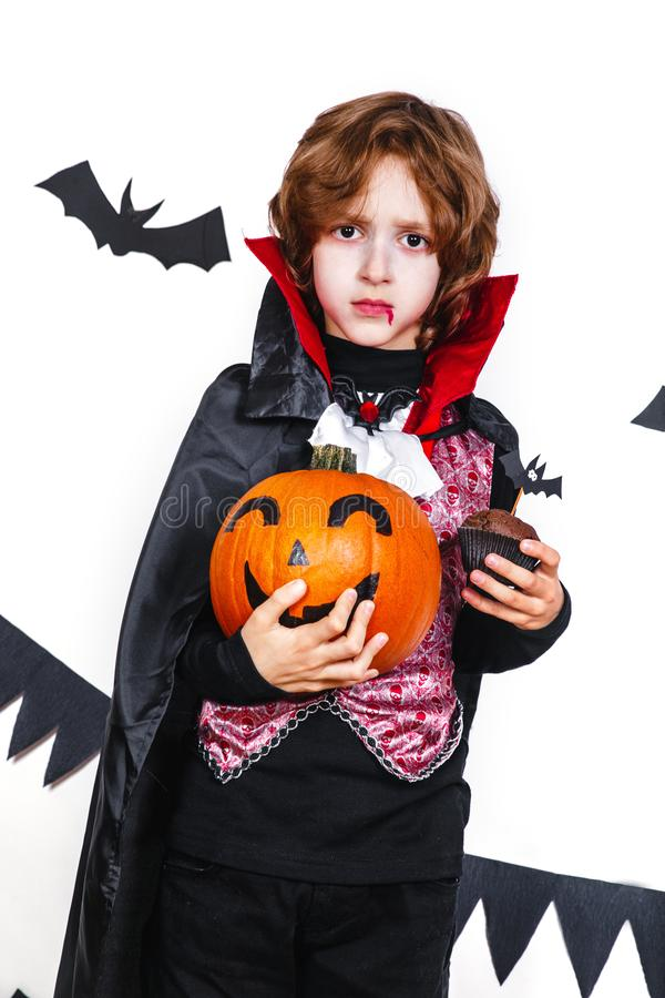 Счастливый мальчик в костюме вампира держа тыкву стоковая фотография rf