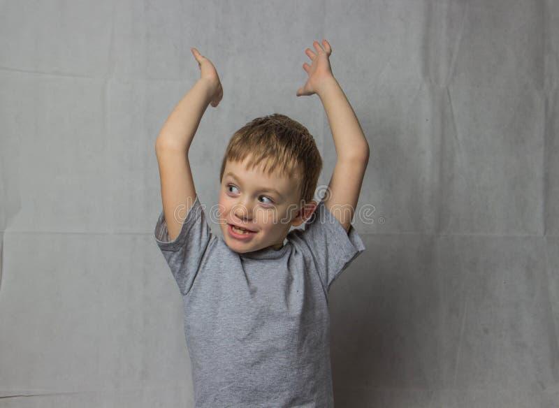 Счастливый мальчик в серой футболке очень счастлив поднимающ его руки вверх стоковое фото rf