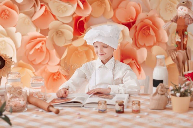 Счастливый мальчик в форме шеф-повара читает поваренную книгу стоковое изображение rf