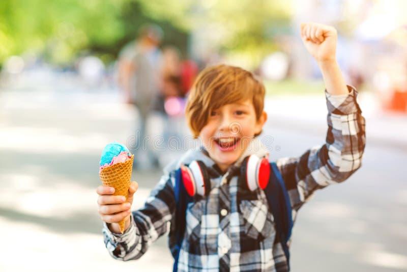Счастливый мальчик ест красочное мороженое в вафле-конусе. Мальчик на Ð стоковые изображения