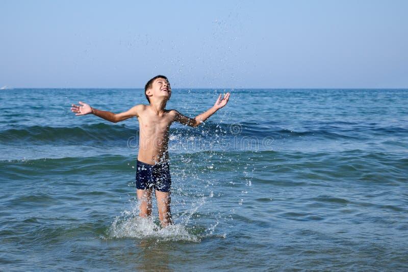 Счастливый мальчик играя в море стоковые фото