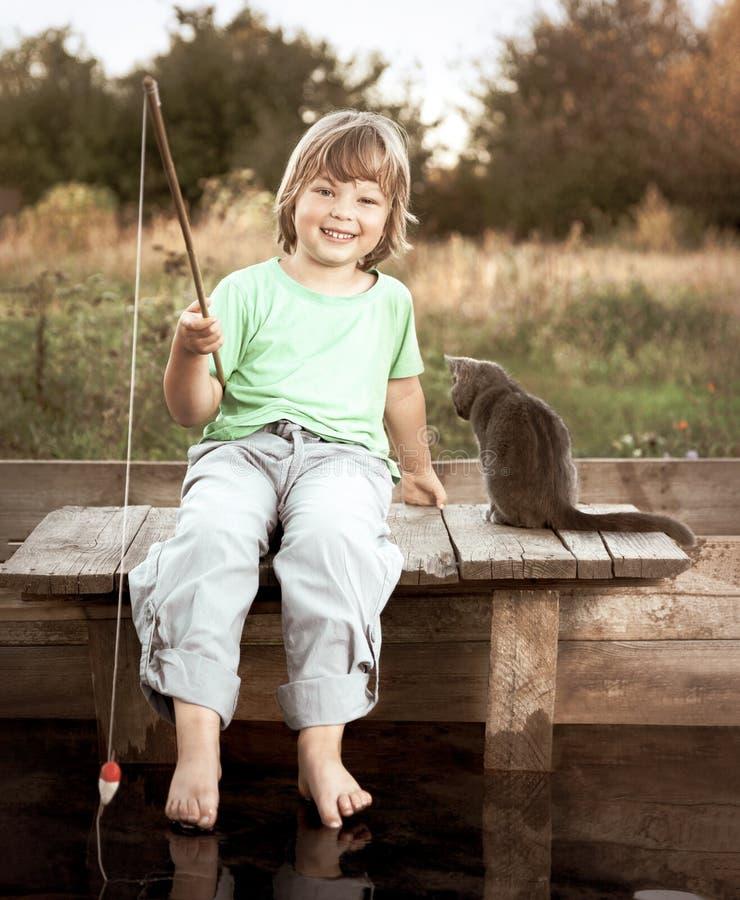 Счастливый мальчик идет удить на реке с любимцем, детьми одним и котенком рыболова с рыболовной удочкой на береге озера стоковое изображение
