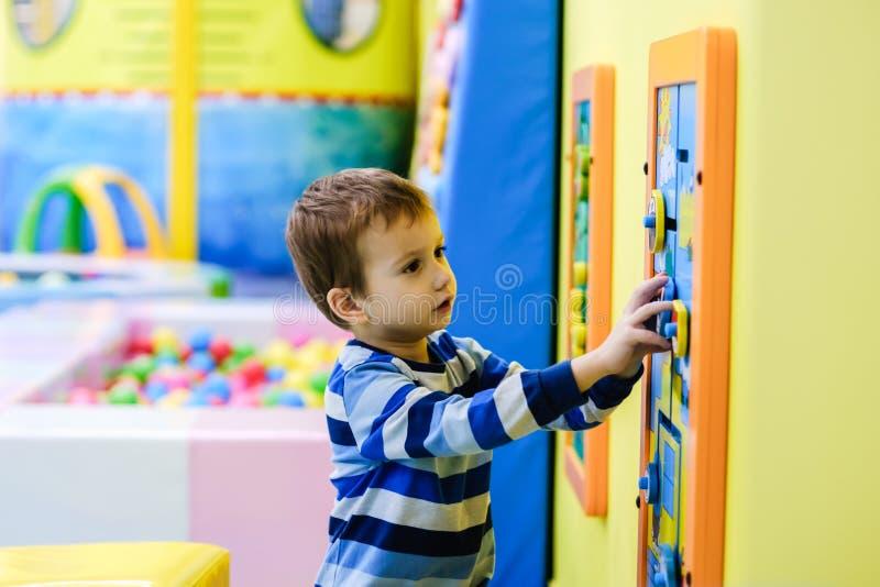 Счастливый мальчик имея потеху в яме шарика в парке атракционов детей и крытом центре игры Ребенок играя с красочными шариками в  стоковая фотография rf