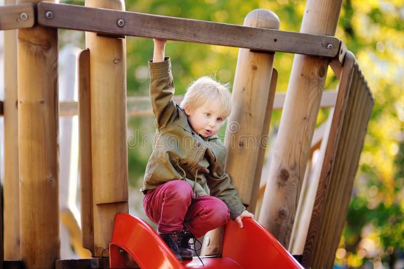 Счастливый мальчик имея потеху на внешней спортивной площадке стоковая фотография