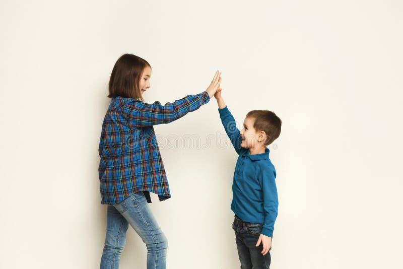 Счастливый мальчик и девушка делая максимум 5, студия стоковые изображения rf
