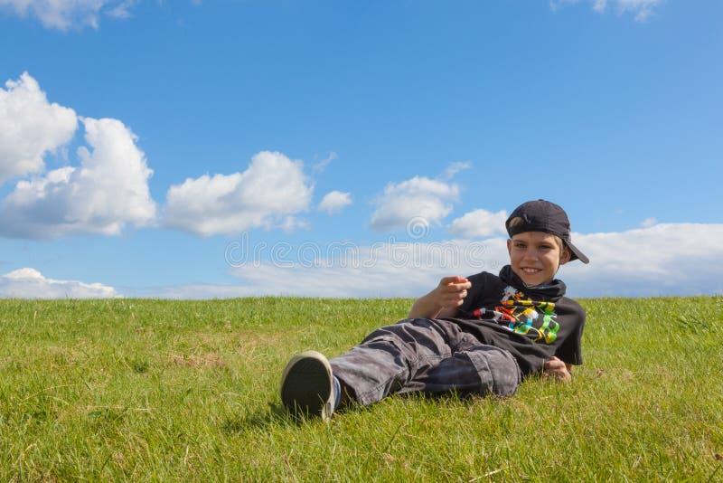 Счастливый мальчик лежа на лужке стоковые фотографии rf