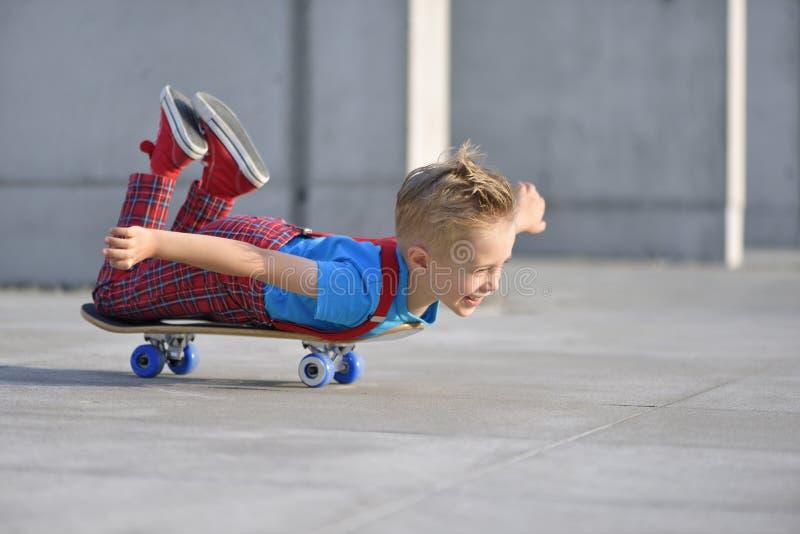 Счастливый мальчик, 5 лет, играя со скейтбордом стоковая фотография rf