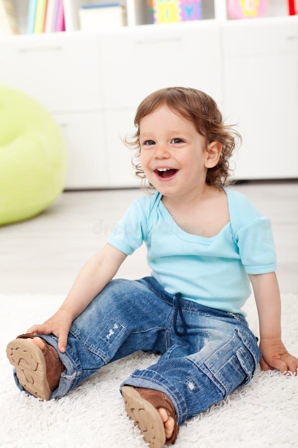 Счастливый мальчик малыша сидя на поле стоковое изображение rf