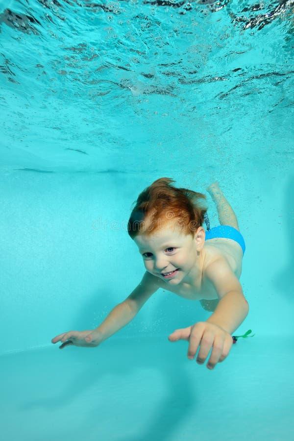 Счастливый мальчик ныряет под водой к дну бассейна на голубой предпосылке и улыбках стоковое фото