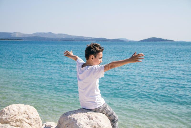 Счастливый мальчик около моря с широкими оружиями стоковые изображения rf