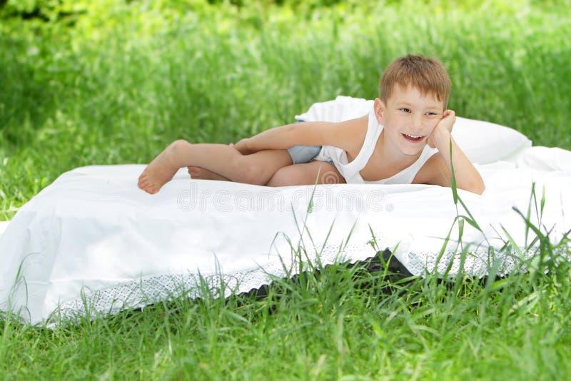 Счастливый мальчик ребенка ослабляя на природе стоковое фото rf