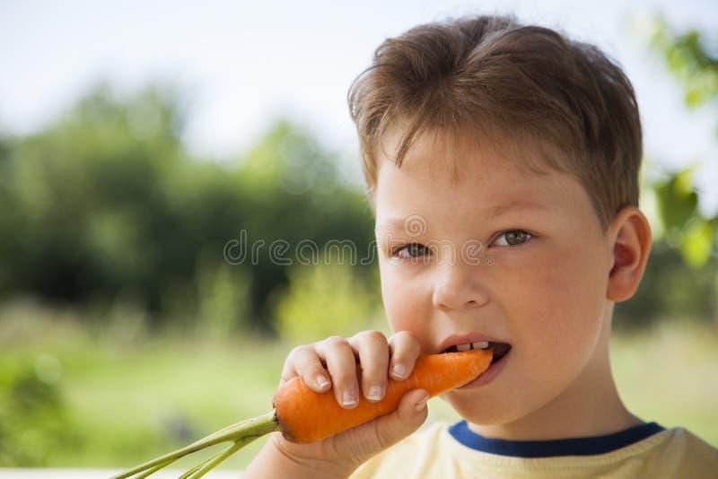 Счастливый мальчик сдерживая морковь, ребенка a с овощем Eatin ребенк стоковая фотография