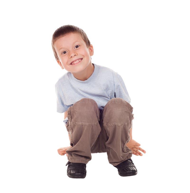 Счастливый мальчик сидит вниз стоковое фото rf