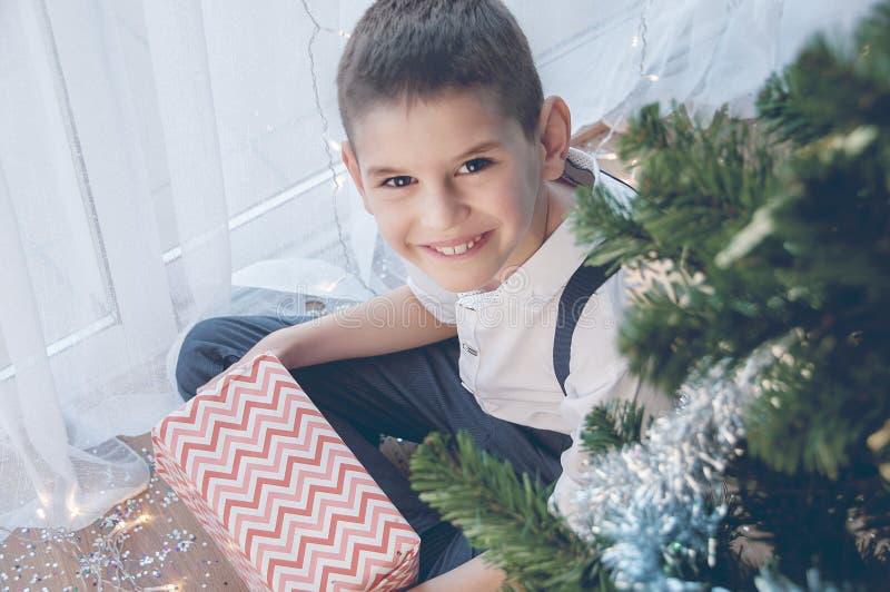 Счастливый мальчик с его подарком рождества Рождество, праздник и подарки стоковое фото rf