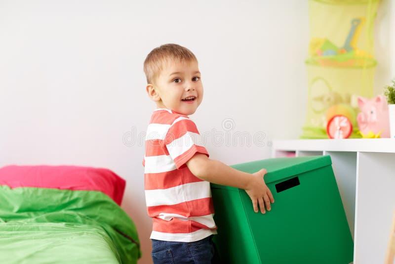 Счастливый мальчик с коробкой для игрушек дома стоковое изображение rf