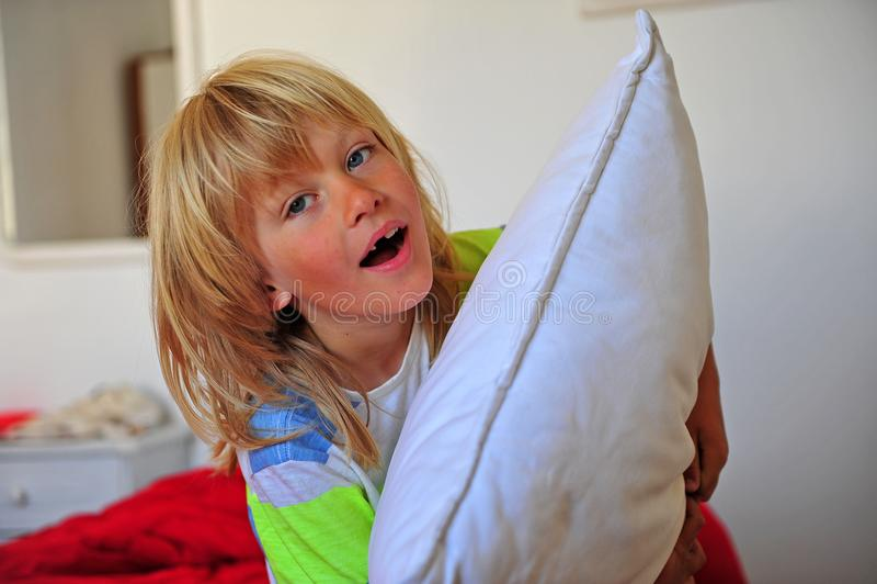 Счастливый мальчик с подушкой в комнате в утре стоковое изображение