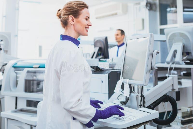 Счастливый медицинский работник делая эксперимент стоковое фото