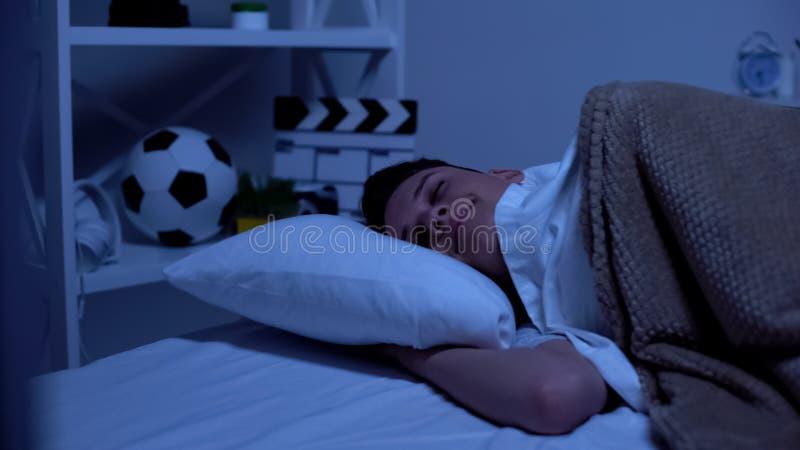 Счастливый многообещающий мальчик лежа в кровати в вечере, времени для релаксации, здорового сна стоковые фотографии rf