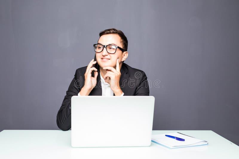 Счастливый молодой бизнесмен говоря на сотовом телефоне и используя компьтер-книжку в офисе стоковые изображения