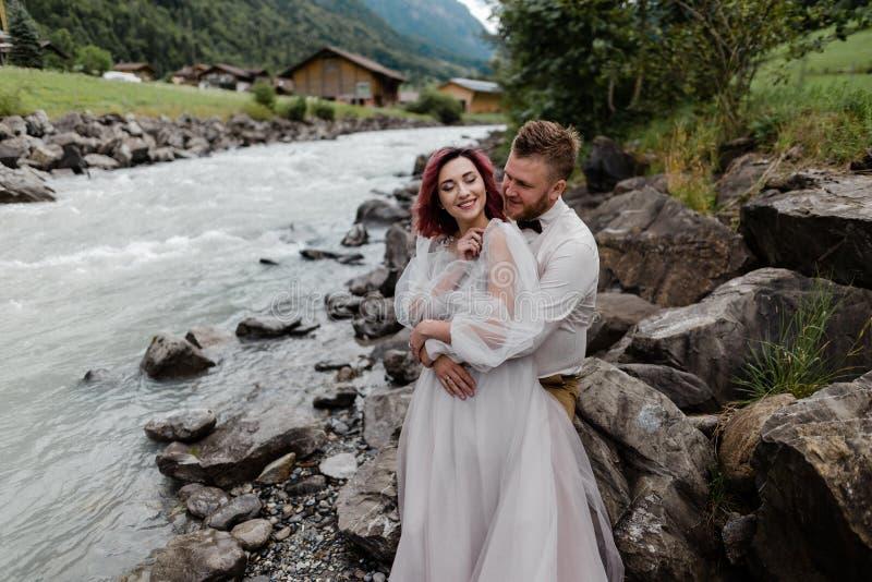 счастливый молодой жених и невеста обнимая пока стоящ на банке быстрого реки горы стоковое фото rf