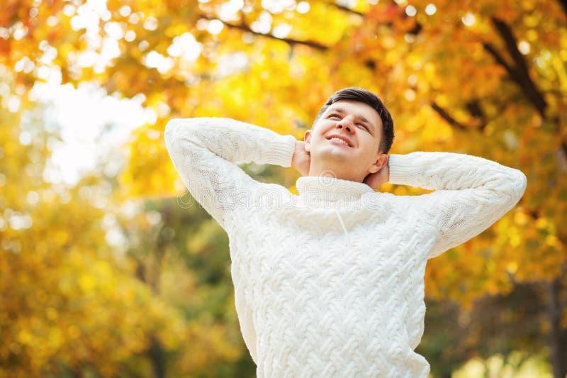 Счастливый молодой кавказский красивый человек оставаясь в парке осени, протягивать и касающей голове Ленивые дни осени стоковая фотография